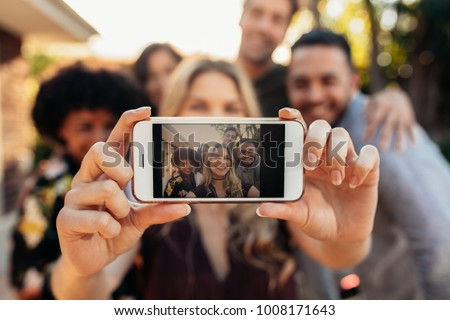 Woman taking self portrait with friends at outdoors party. Focus on mobile phone in hands of female.