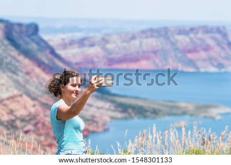 Woman taking selfie picture of Sheep Creek Overlook in Manila, Utah near Flaming Gorge National Park with cloudy valley and river