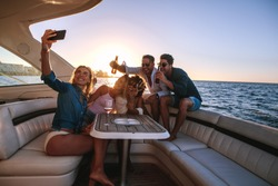 Woman taking selfie with friends in boat party. Group of young people on yacht with drinks and taking selfie.