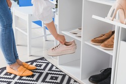 Woman taking shoes from stand in hall