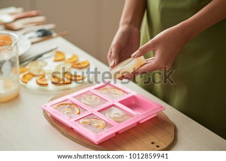 Woman taking soap bars out of plastic form