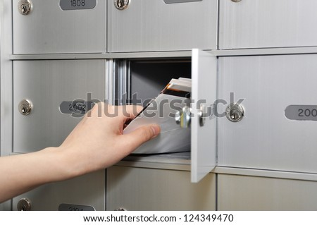 Woman taking some letters from mailbox - stock photo