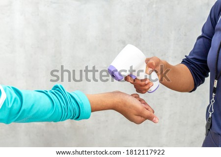 Woman taking temperature with digital thermometer to a person. Taking temperature in a workout Foto stock ©