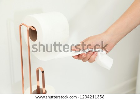 Woman taking toilet paper from roll holder in bathroom, closeup #1234211356