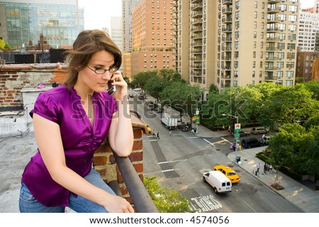 Woman talking on cell phone on city roof.