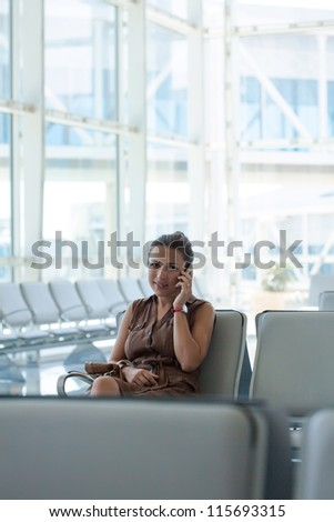 Woman Talking On  Phone At Departure Lounge