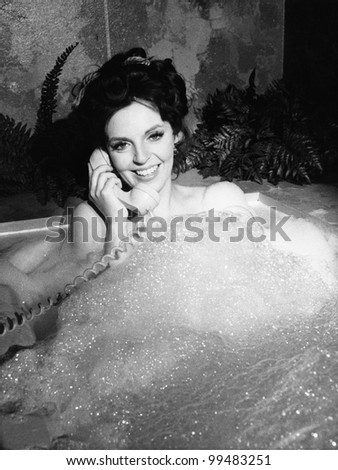Woman talking on phone in bubble bath