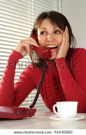 Woman talking on the phone near the window