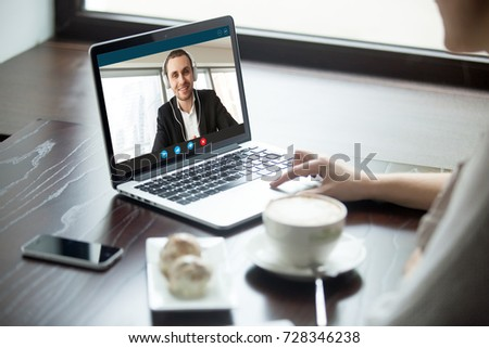 Woman talking to man in headphones via video call. Remote co-workers chatting, learning and exchanging foreign languages, girl watching business webinar online in cafeteria. Close up, focus on screen.