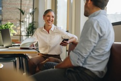 Woman talking with coworker at office desk. Businesswoman having discussion with team member in office.