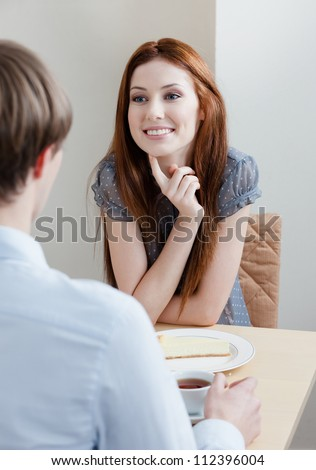 Woman talks with man sitting at the table at the bar