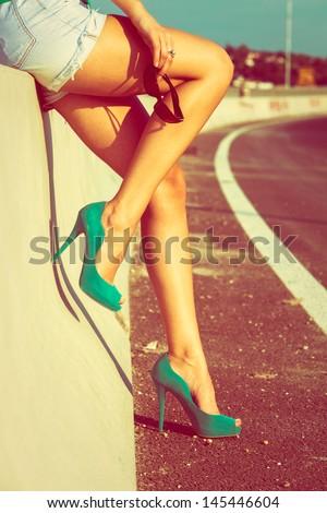 woman tan legs in high heel green shoes outdoor shot  summer day