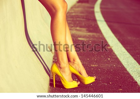 woman tan legs in high heel yellow shoes outdoor shot  summer day