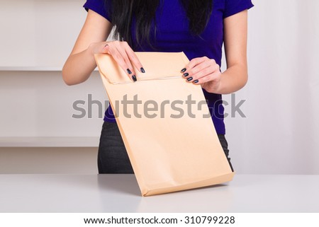 Woman tape the large envelope with documents before sending