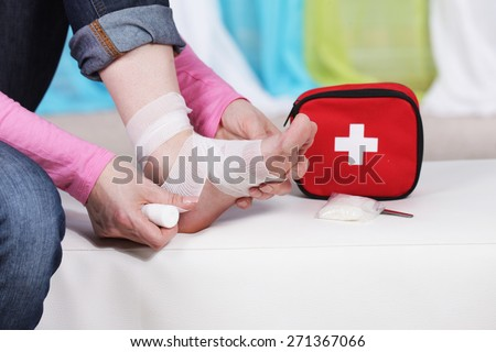Woman taping her foot with bandage
