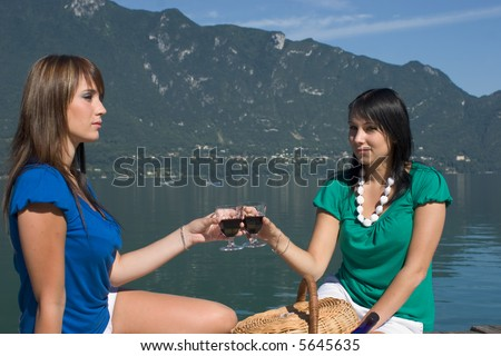 Woman tasting of the wine at the edge of a lake