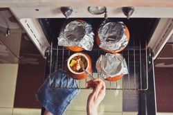 Woman tasting stewed or baked potatoes in brown ceramic pots when taking out of oven. Low DOF. Top view.