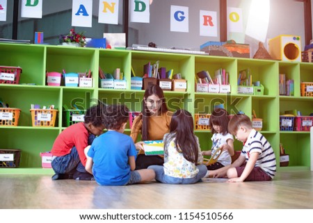 woman teacher in classroom teaching preschool kids, joyful learning together with mixed-race international children
