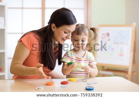 Woman teacher play with preschooler child in day care center.