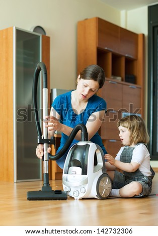 Woman teaches child to use the vacuum cleaner in living room