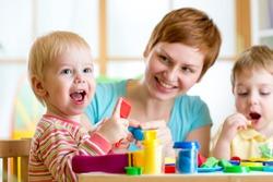 woman teaches kids handcraft at kindergarten or playschool