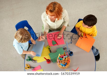 Woman teaching and helping boys in elementary school art class