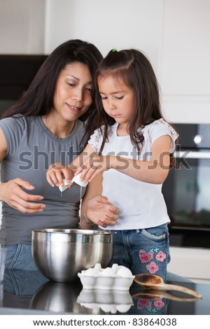 Woman teaching child to prepare dough with healthy ingredients #83864038