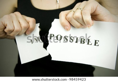 woman tearing word impossible to transform into possible - stock photo