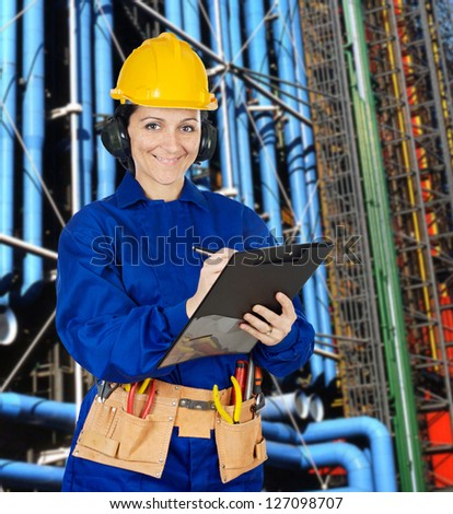 Woman technician with a clipboard in the refinery