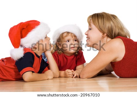 Woman telling a christmas story to her kids laying on the floor - isolated