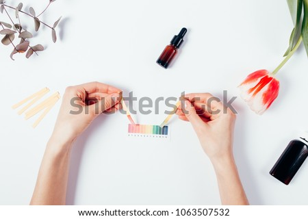 Woman testing cosmetics by using litmus papers and scale. Top view of female hands measuring of pH level among tulip, eucalyptus branch on white background, flat lay composition.