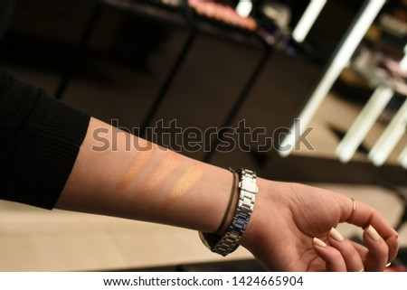 Woman testing make up on her hand. Swatches comparison. Light, medium, dark. Bronzing, blusher, compact products. Copy space, design space. #1424665904