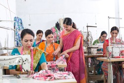 Woman textile worker checking garment stock at factory