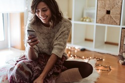 Woman texting in a smartphone - Christmas and Winter Season