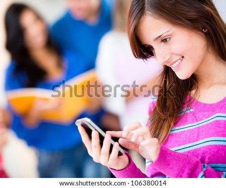 Woman texting on her cell phone and smiling
