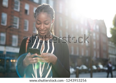 Woman texting on her phone in the city