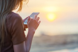 woman texting on smart phone on the beach during sunset