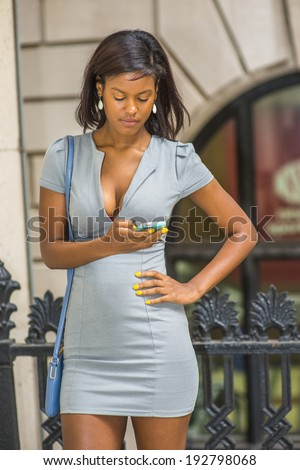 Woman texting outside. Wearing a gray business dress, drop earrings, carrying a shoulder small bag, a young beautiful black businesswoman is looking down, reading messages on her cell phone.
