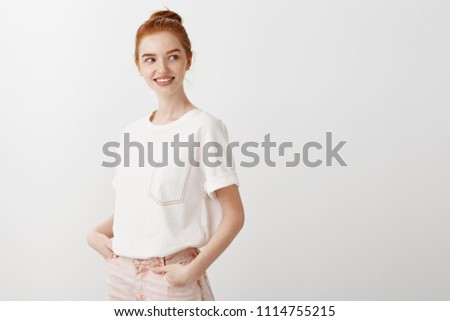 Woman thinking about grabbing drink on way home. Charming carefree and relaxed female redhead in stylish t-shirt and jeans, holding hand in pocket, standing half-turned and gazing right with smile