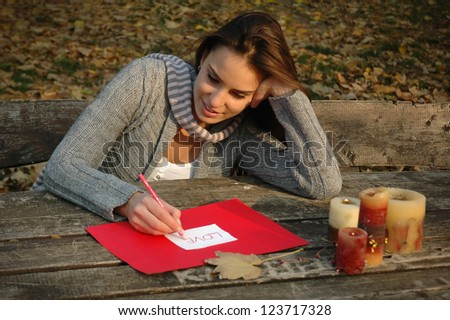 woman thoughtfully smiling, leaning on the arm, writing word LOVE on white and red paper on wooden table with candles