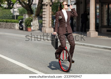 woman through the city with the unicycle to go to work, outdoor #233990947