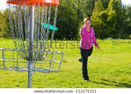 Woman throwing a disc to the disc basket