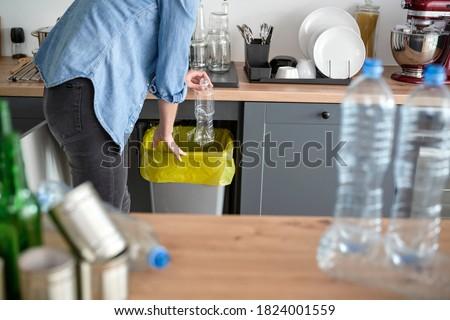Woman throwing away plastic bottle into yellow bin Stockfoto ©
