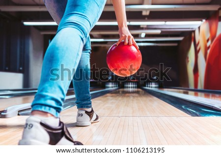 Woman throwing ball in bowling club. View from behind