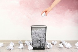 Woman throwing crumpled paper ball into basket near pink wall, closeup