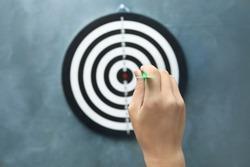 Woman throwing green arrow at dart board on grey background, closeup