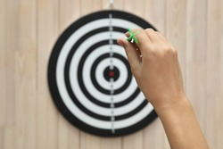 Woman throwing green arrow at dart board on wooden background, closeup