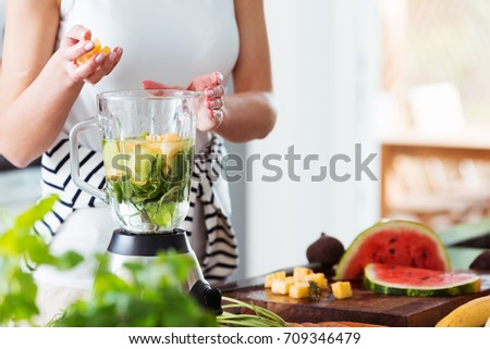 Woman throwing pineapple cubes into mixer with water and mint while preparing energetic smoothie