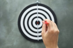 Woman throwing red arrow at dart board on grey background, closeup
