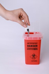 Woman throwing used syringe into sharps container on white background, closeup